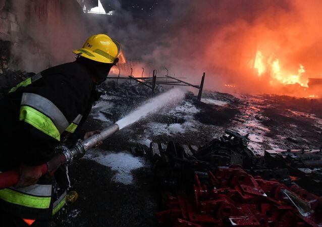 Bombeiro apaga incêndio em fábrica de algodão na aldeia de Azat Karagoinly no Azerbaijão, causado por bombardeiro