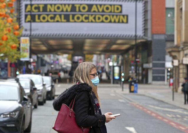 Mulher caminha com máscara para evitar contágio pelo coronavírus na cidade de Manchester, no Reino Unido