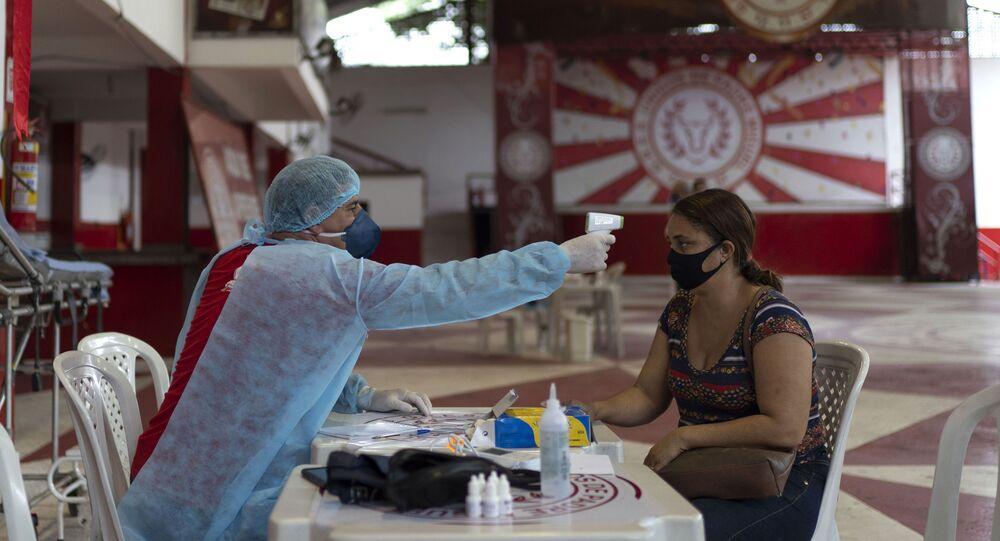 No Rio de Janeiro, um médico checa possíveis sintomas de COVID-19 em uma mulher na quadra da escola de samba Unidos de Padre Miguel, em 24 de maio de 2020