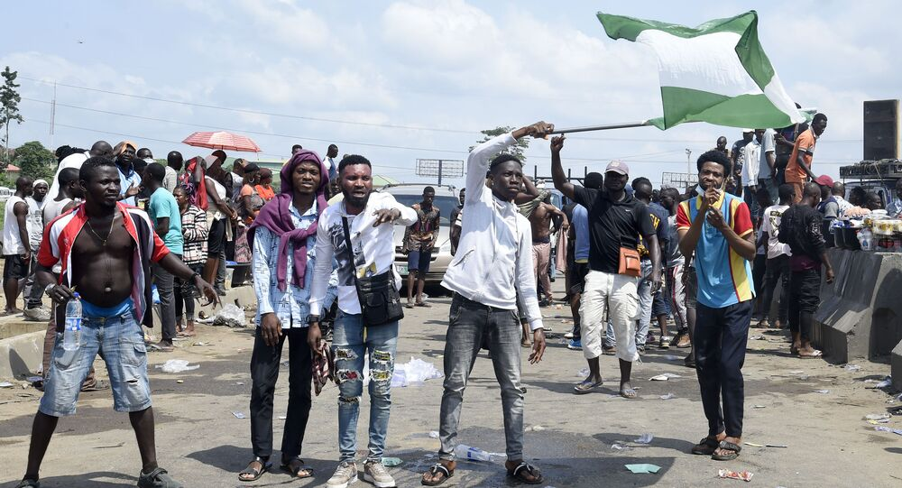Manifestantes exibem a bandeira da Nigéria em Lagos durante protesto contra violência policial