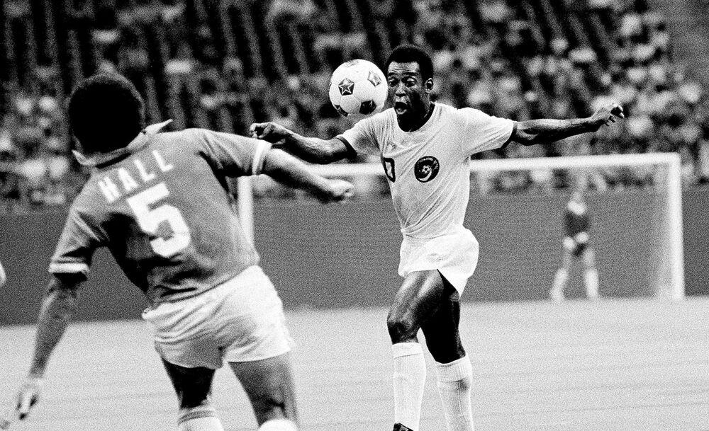 O craque do New York Cosmos, Pelé, observa a bola enquanto Dallas Tornado, Dick Hall, se apressa para bloqueá-lo em 27 de julho de 1975 em Irving, Texas
