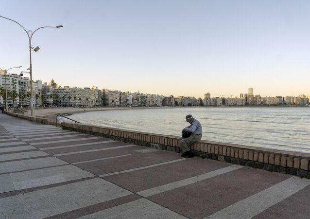 Homem sentando na praia de Pocitos, no Uruguai