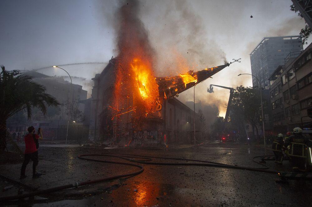 A cúpula da igreja de Assunção cai em chamas após ser incendiada por manifestantes na comemoração do primeiro aniversário da insurreição social no Chile