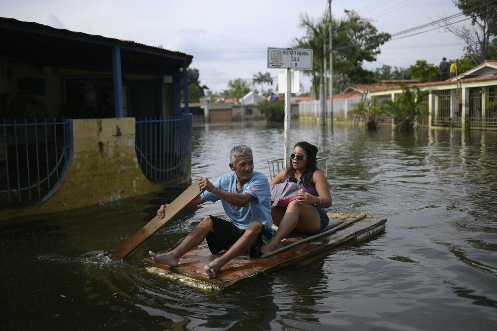 Homem utiliza porta como jangada improvisada enquanto transporta uma mulher pelas ruas inundadas no bairro Mata Redonda, em Maracay, Venezuela