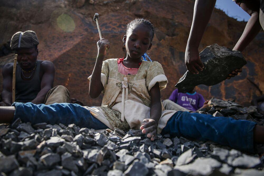 Menina durante o trabalho em uma pedreira em Nairóbi, Quênia