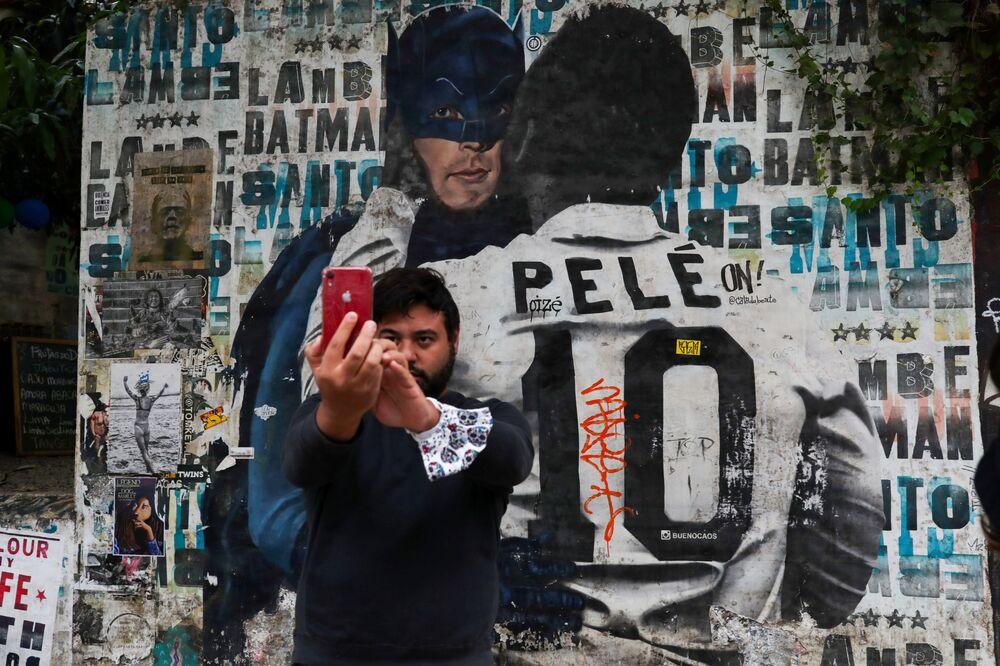 Homem tira selfie perto de um mural que retrata a lenda do futebol brasileiro Pelé.