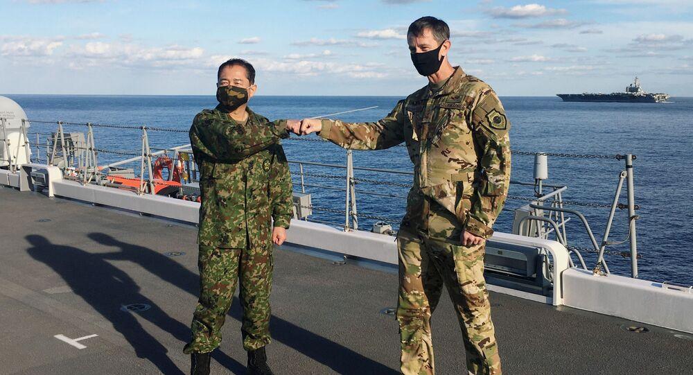 Tenente-general Kevin Schneider, comandante das Forças Armadas dos EUA no Japão, e o general Koji Yamazaki, comandante-chefe do Estado-Maior Conjunto do Japão, se cumprimentam no destróier porta-helicópteros da Força Marítima de Autodefesa do Japão JS Kaga durante os exercícios militares Keen Sword, em meio à doença do coronavírus (COVID-19), no mar ao sul do Japão, 26 de outubro de 2020