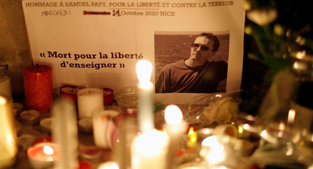 Morto pela liberdade de ensinar, escrito à esquerda da fotografia do professor francês assassinado, colocada entre velas em tributo nacional