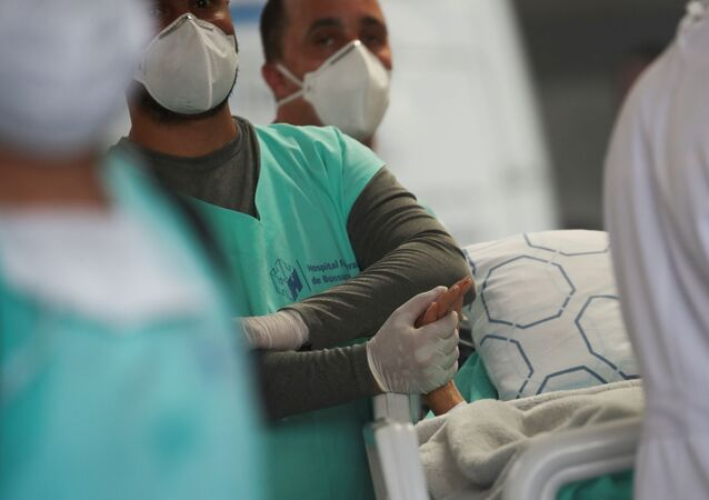 Profissional de saúde segura mão de paciente durante evacuação do Hospital Federal de Bonsucesso, no Rio de Janeiro, 27 de outubro de 2020