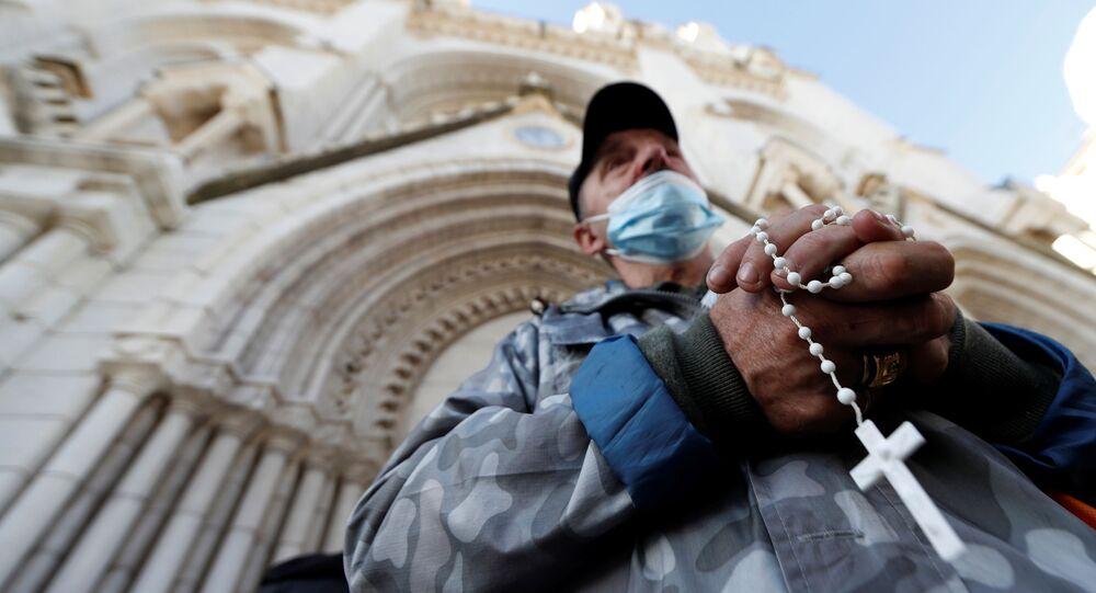 Homem reza pelas vítimas do ataque de 29 de Outubro em frente da catedral de Notre Dame
