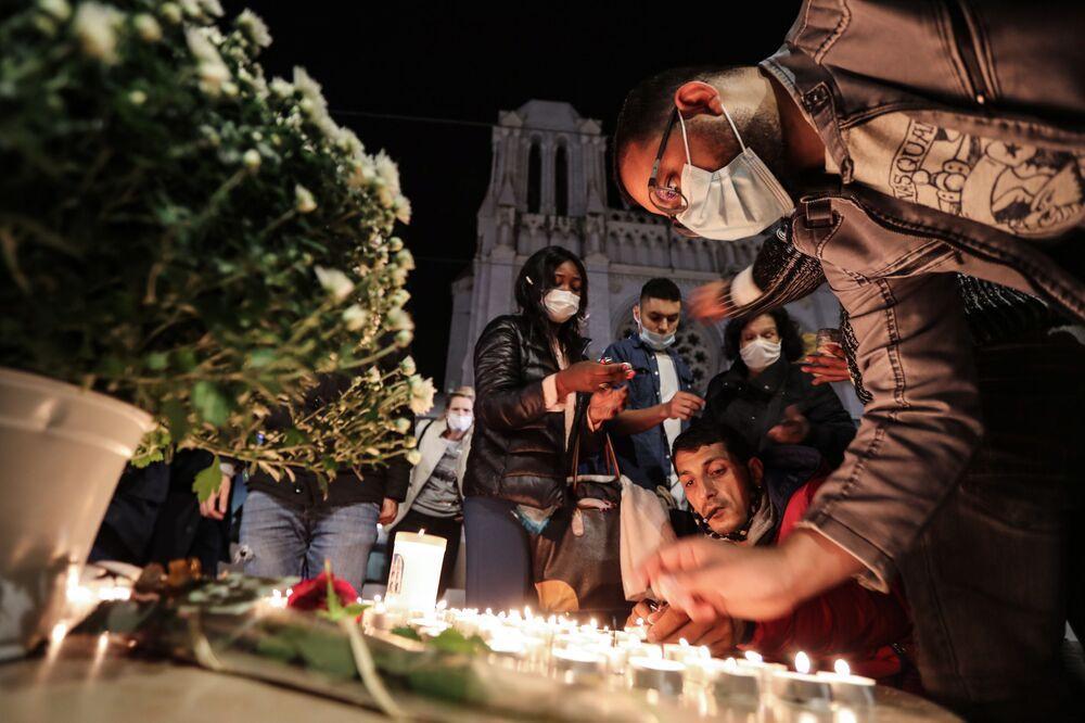Pessoas acendem velas fora da Basílica Notre-Dame de Assunção em Nice, 29 de outubro de 2020, em memória de três vítimas do atacante com faca, que cortou a garganta de pelo menos uma mulher no interior da igreja, na cidade da Riviera Francesa