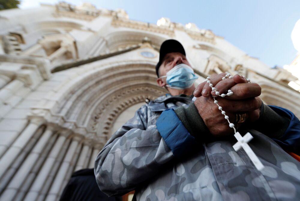 Homem reza em frente à Basílica de Notre-Dame para prestar homenagem às vítimas do ataque mortal com faca em Nice, França, 30 de outubro de 2020