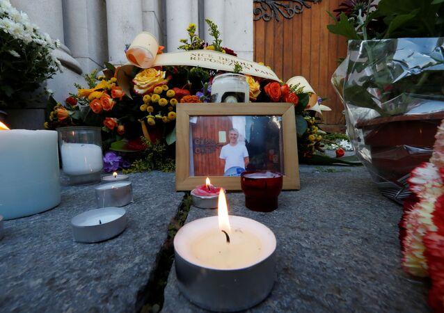 Retrato de Vincent Loques, o sacristão da Basílica de Notre-Dame, uma das vítimas do ataque mortal com faca, é visto com velas e flores em frente à Basílica de Notre-Dame em Nice, França, 30 de outubro de 2020
