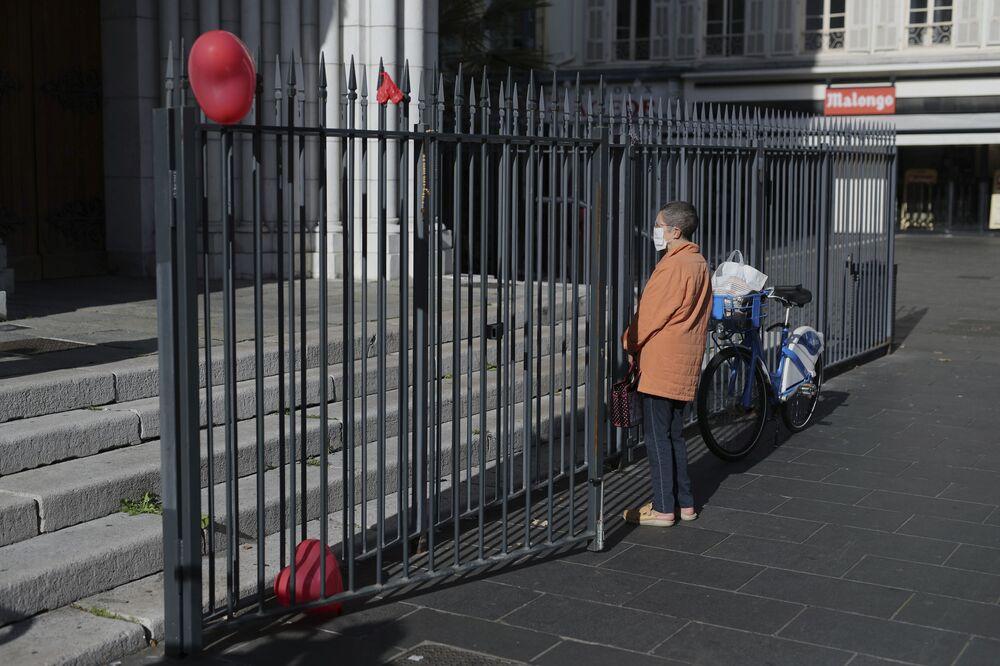 Mulher olha para a entrada da Basílica de Notre-Dame, em Nice, França, 30 de outubro de 2020