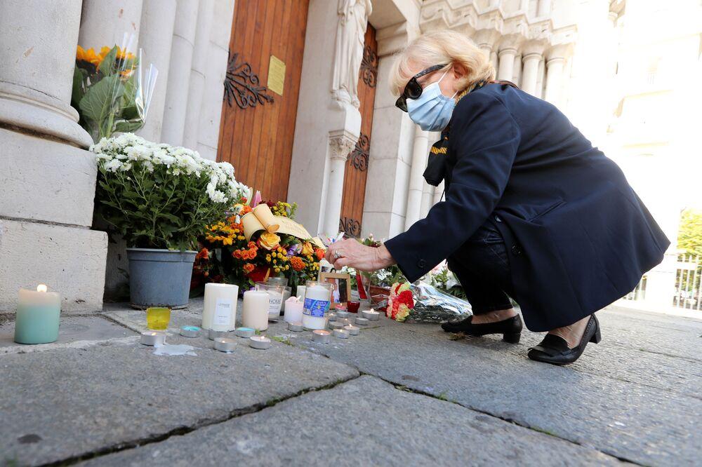 Mulher acende velas fora da Basílica Notre-Dame de Assunção, em Nice, em 30 de outubro de 2020, em homenagem às três vítimas do atacante com faca, que cortou a garganta de pelo menos uma mulher, no interior da igreja na cidade da Riviera francesa