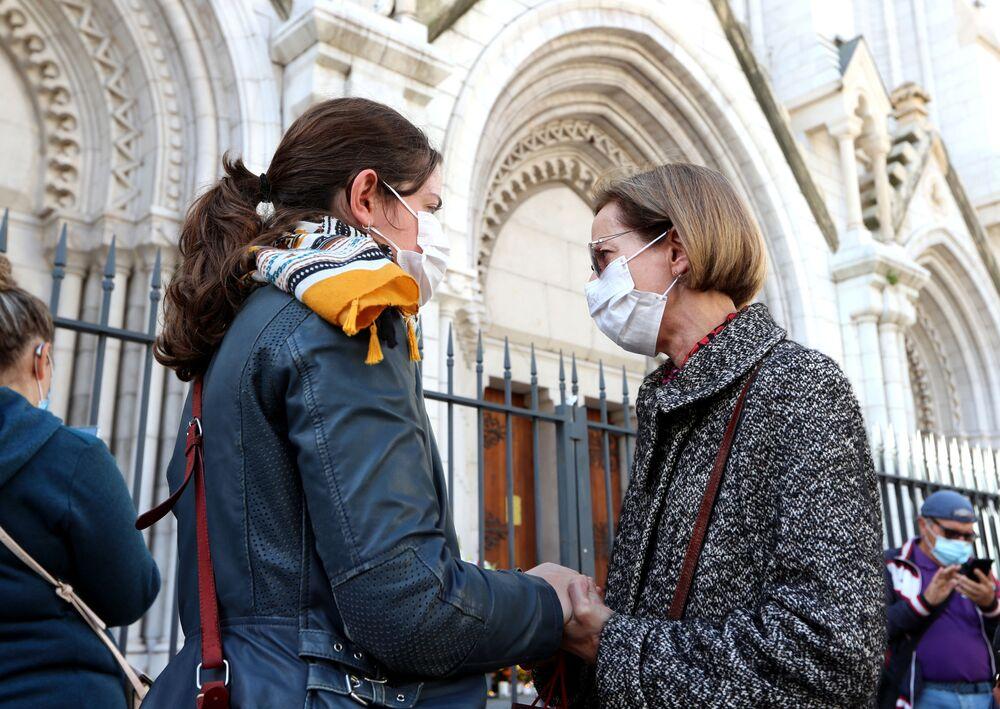 Duas mulheres seguram as mãos em frente à Basílica de Notre-Dame em Nice, em 30 de outubro de 2020, durante uma homenagem às vítimas mortais do atacante com faca no dia anterior