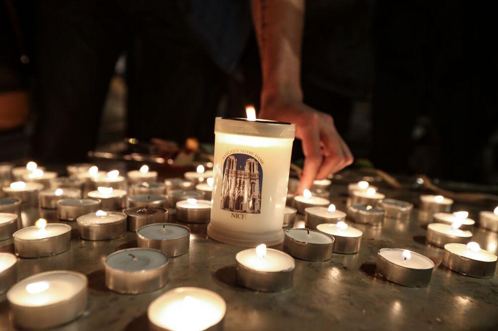 Pessoas acendem velas fora da Basílica Notre-Dame de Assunção em Nice, em 29 de outubro de 2020, em homenagem às três vítimas do atacante com faca, que cortou a garganta de pelo menos uma mulher, no interior da igreja na cidade da Riviera francesa