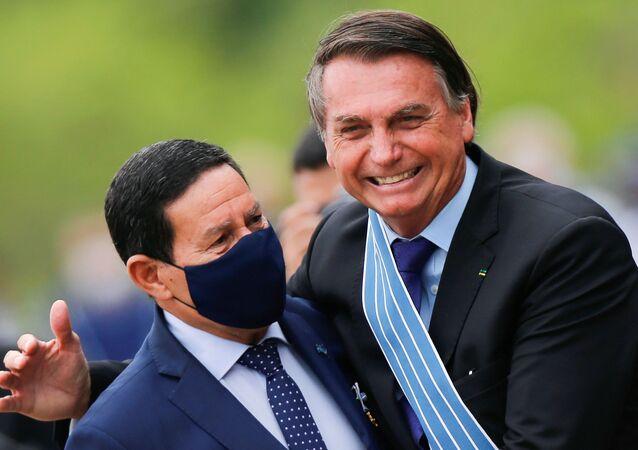 O presidente do Brasil, Jair Bolsonaro, abraça o vice-presidente do Brasil, Hamilton Mourão, durante a cerimônia do Dia do Aviador na Base Aérea de Brasília em 23 de outubro de 2020.