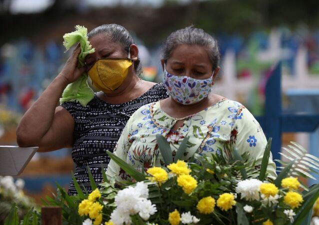 Parentes de vítimas da COVID-19 em cemitério no Brasil