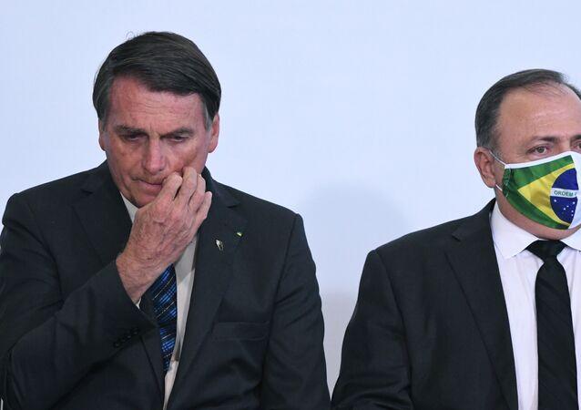 Em Brasília, o presidente brasileiro, Jair Bolsonaro (à esquerda), e o ministro da Saúde, Eduardo Pazuello (à direita), participam de cerimônia no salão nobre do Palácio do Planalto, em 14 de outubro de 2020