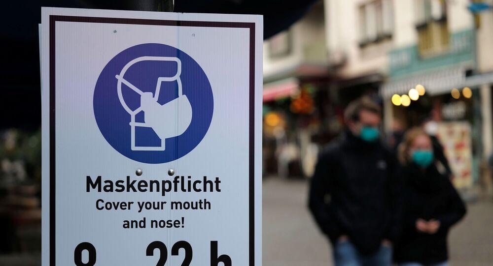 Em Frankfurt, pessoas usam máscaras enquanto caminham ao lado de uma placa pedindo que as pessoas cubram seus narizes e bocas em meio à pandemia da COVID-19, em 27 de outubro de 2020