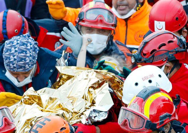 Bombeiros garota de três anos nos escombros de terremoto na Turquia na cidade de Izmir.