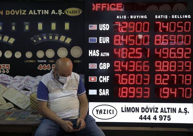Homem diante de casa de câmbio na Turquia com cotações da lira