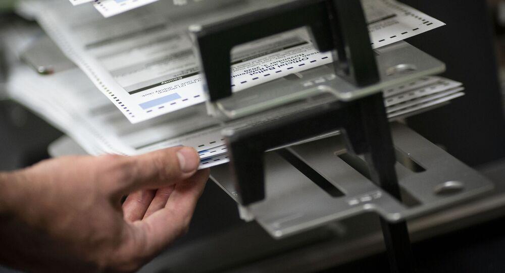 Funcionários do sistema eleitoral de Wisconsin contam cédulas de eleitores ausentes, em Kenosha, Wisconsin, EUA, 3 de novembro de 2020