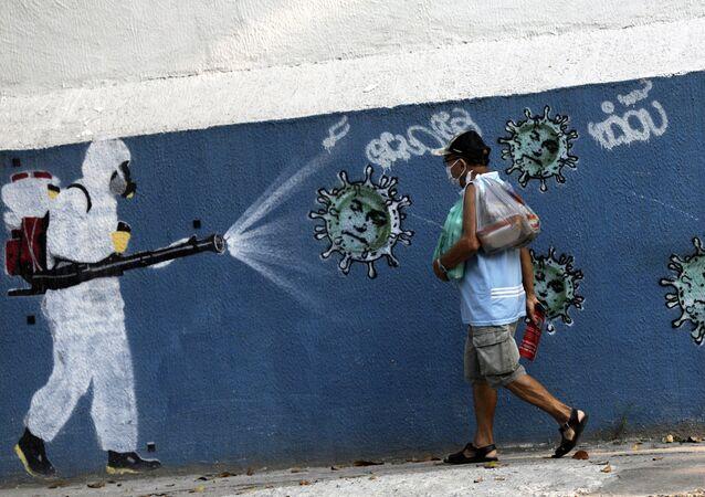 Um homem caminha ao lado de um grafite retratando um limpador em equipamento de proteção espalhando vírus com o rosto do presidente Jair Bolsonaro, em meio ao surto da doença coronavírus (COVID-19), no Rio de Janeiro, Brasil, 7 de outubro de 2020