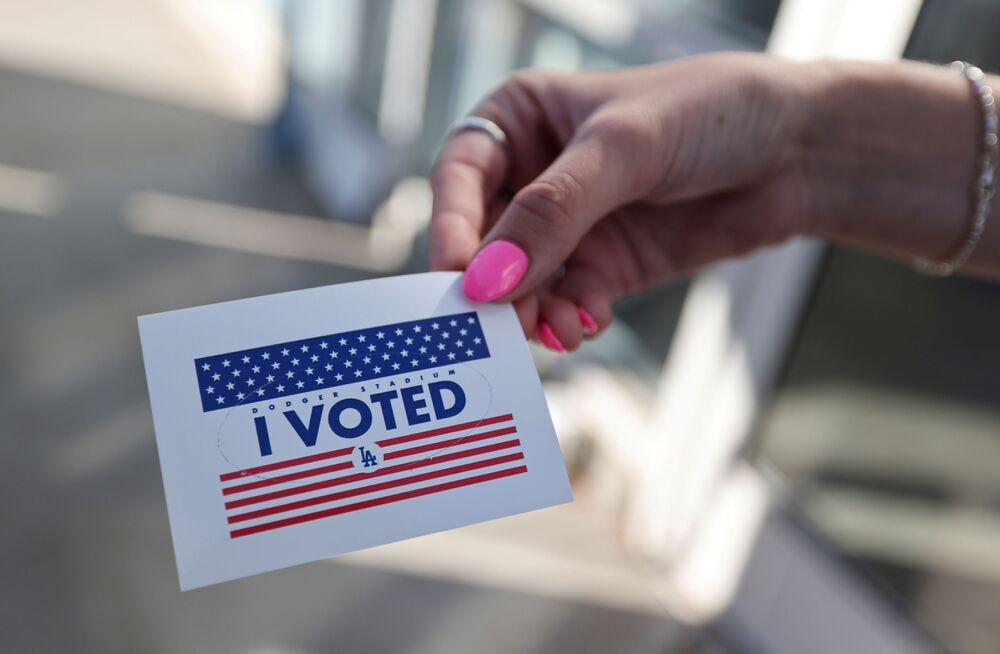 Pessoa exibe etiqueta Eu votei, enquanto cidadãos votam nas eleições do presidente dos EUA no primeiro dia de votação presencial alargada em meio à pandemia da COVID-19, em Los Angeles, Califórnia, EUA, 30 de outubro de 2020