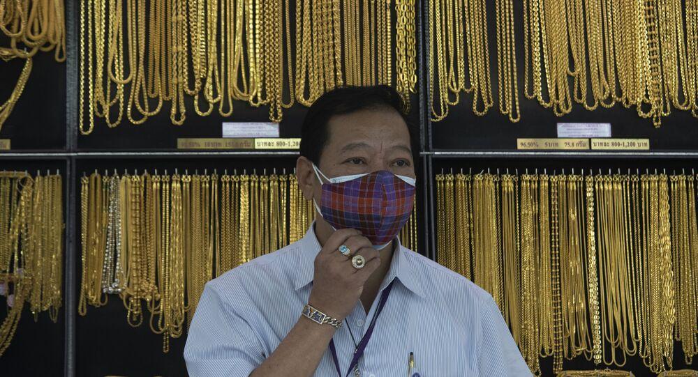 Vendedor na Tailândia usando máscara contra a COVID-19 diante de artigos de ouro
