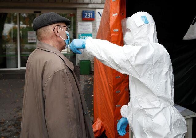 Enfermeiro tira temperatura de um homem em frente a um hospital em Varsóvia