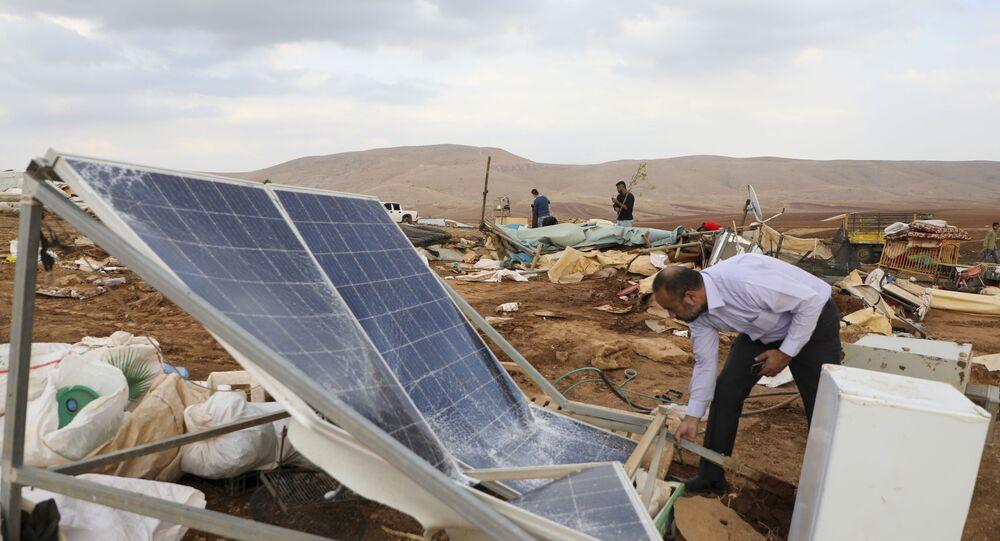 Palestino observa estruturas de tendas palestinas destruídas por Israel na Cisjordânia
