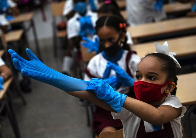 Aluna usa máscara e luvas em uma escola de Havana, Cuba