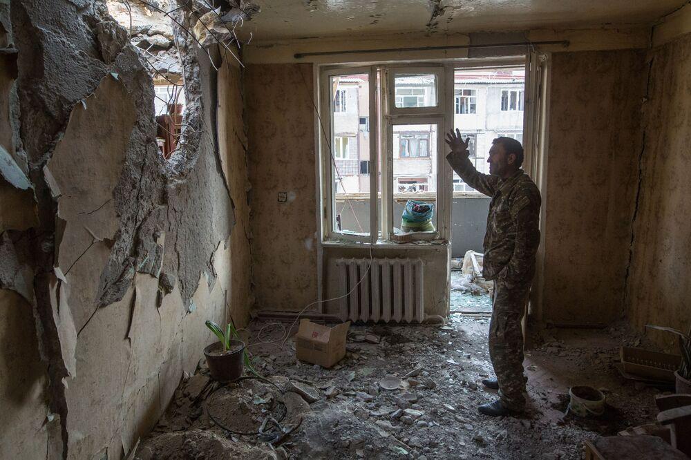 Homem é fotografado em um apartamento em ruínas em Stepanakert, Nagorno-Karabakh, enquanto região vive conflito armado entre azeris e armênios