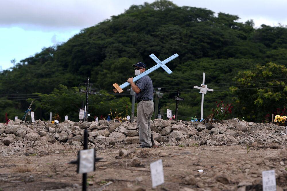 Homem com cruz olha para sepulturas no cemitério COVID-19 no Dia dos Mortos em Honduras