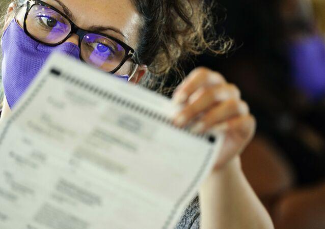 Funcionária do sistema eleitoral do estado norte-americano da Geórgia examina cédula, em Atlanta, 5 de novembro de 2020