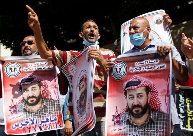 Manifestantes seguram fotos do prisioneiro palestino em greve de fome Maher Al-Akhras, detido por Israel, durante uma manifestação de solidariedade a Al-Akhras, na cidade de Gaza, em 12 de outubro de 2020. REUTERS / Mohammed Salem