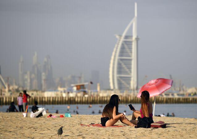 Mulheres tomam banho de sol em Dubai, Emirados Árabes Unidos, tendo ao fundo o hotel Burj al-Arab (foto de arquivo)
