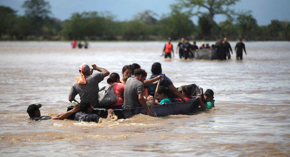 Pessoas afetadas pela enchente pegam um barco para atravessar uma rua após a passagem da Tempestade Eta, em La Lima, Honduras, 7 de novembro de 2020.