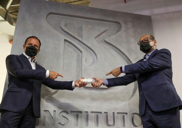 Governador do estado de São Paulo, João Dória (à esquerda) e o diretor do Instituto Butantan, Dimas Covas, seguram dose da vacina chinesa CoronaVac, São Paulo, 9 de novembro de 2020