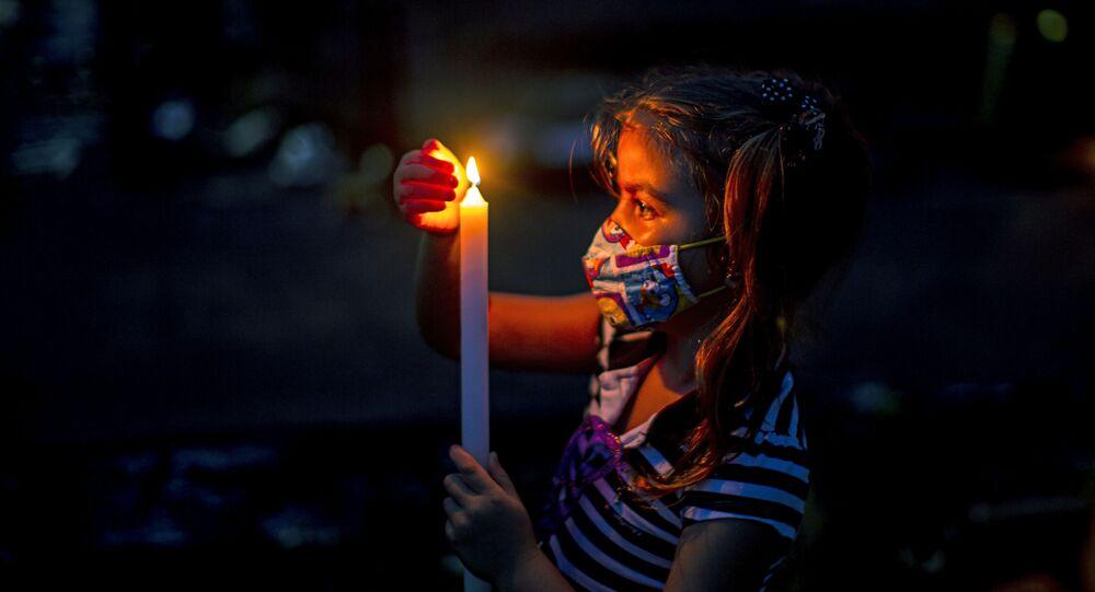 Menina segura vela em cemitério de Belém, no estado do Pará, 2 de novembro de 2020