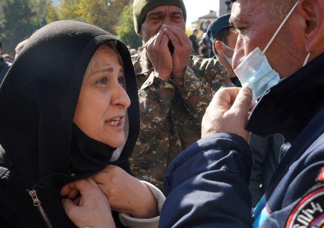 Mulher discute com agente de segurança durante protestos em Erevan, capital da Armênia, 11 de novembro de 2020