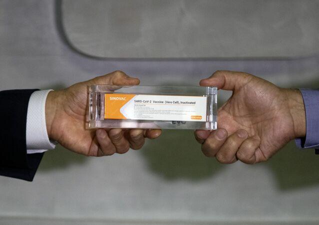 Governador de São Paulo, João Doria (à esquerda), e diretor do Instituto Butantan, Dimas Covas (à direita), mostram dose da vacina CoronaVac, São Paulo, 9 de novembro de 2020