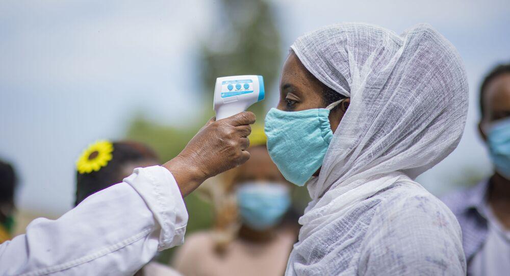 Agente de saúde mede temperatura de moradora na capital da província de Tigré Mekelle, Etiópia, 9 de setembro de 2020
