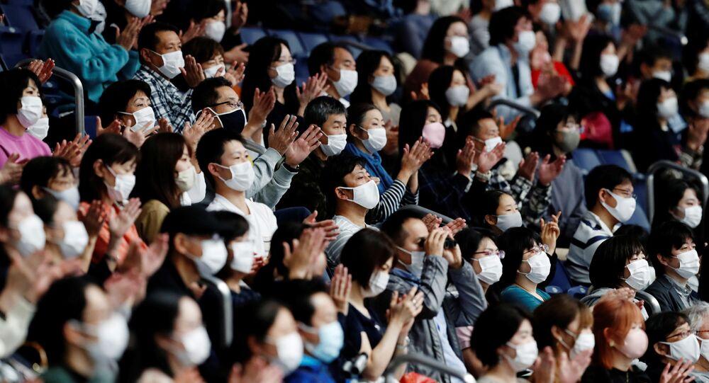 Espectadores usam máscaras de proteção durante evento esportivo em Tóquio