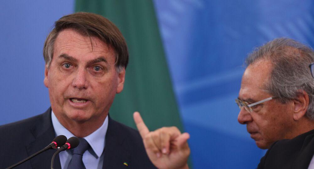 Presidente Jair Bolsonaro e o ministro da Economia, Paulo Guedes, ao lado do intérprete de libras durante pronunciamento à imprensa no Palácio do Planalto, em Brasília (DF), para falar sobre as medidas de combate ao coronavírus