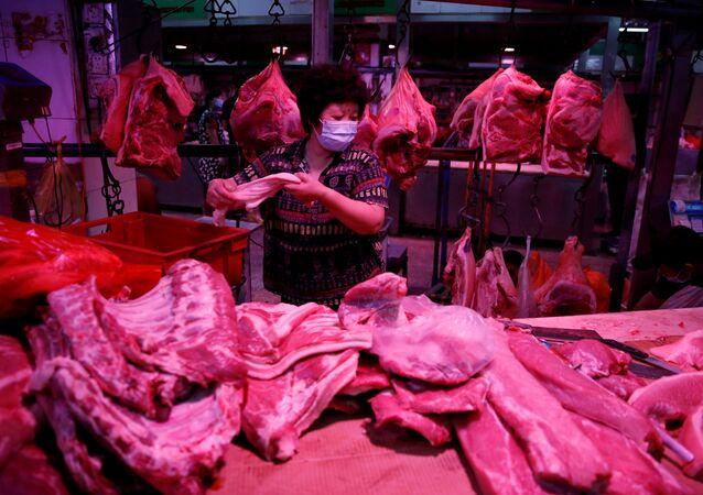 Vendedora usa máscara enquanto prepara carne de porco dentro do mercado atacadista de Yuegezhuang, após novos casos de infecções pela doença do novo coronavírus (COVID-19) em Pequim, China, 17 de junho de 2020
