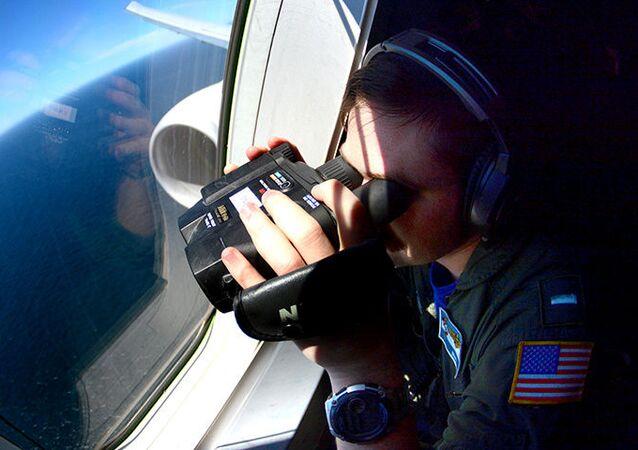 Membro da Marinha dos EUA, a bordo do avião Boeing P-8A Poseidon, olha para baixo enquanto sobrevoa o Atlântico Sul durante a busca pelo submarino ARA San Juan, desaparecido no mar, Argentina, 26 de novembro de 2017