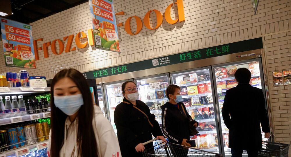 Chineses diante de produtos congelados num supermercado em Pequim